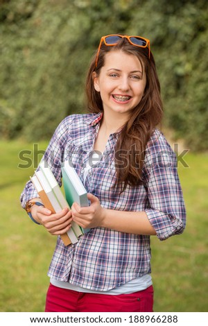 Cheerful teenage student with braces holding books at park