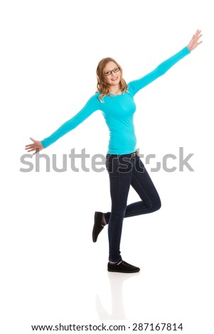 Cheerful teenage woman with arms wide open - stock photo