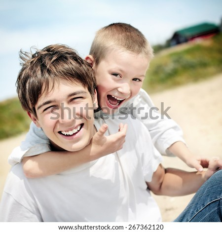 Cheerful Teenager and Kid Portrait Outdoor - stock photo