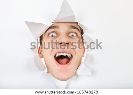 Cheerful Teenager peeking through Paper Hole - stock photo