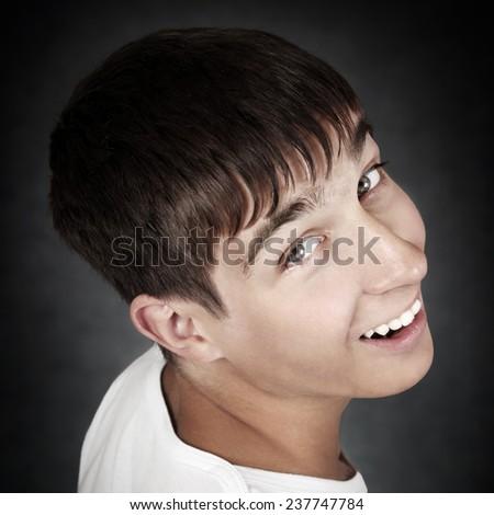 Cheerful Teenager Portrait on the Dark Background Closeup - stock photo