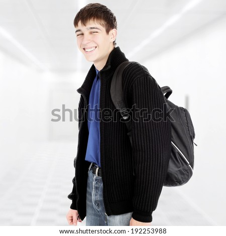 Cheerful Teenager with Knapsack in the White Corridor - stock photo