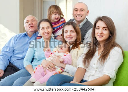 cheerful three generations family sits on sofa in livingroom