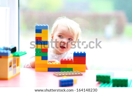 Cheerful toddler girl building house from plastic blocks sitting next to a big window - stock photo