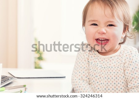 Cheerful toddler girl with a huge smile sitting at a desk in her house - stock photo