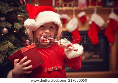 Cheerful toddler girl with Christmas candy and present  - stock photo