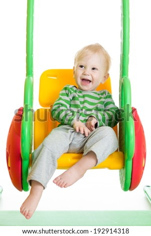 cheerful toddler kid playing on the swings - stock photo
