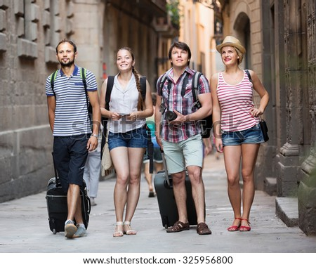 Cheerful tourists walking the street with luggage at vacation - stock photo