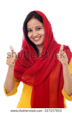Cheerful traditional woman showing thumb up symbol by two hands - stock photo