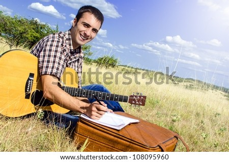Cheerful traveling musician writes a song on sunny day - stock photo