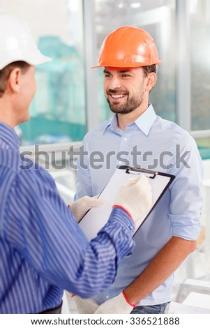 Cheerful two engineers are discussing building of a construction. They are looking at each other and smiling. The senior man is standing and drawing a sketch - stock photo