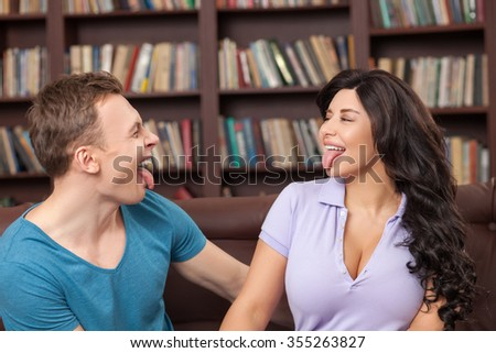 Cheerful two friends are showing tongue to each other. They are drawing faces and laughing. The man and woman are sitting on sofa in the library