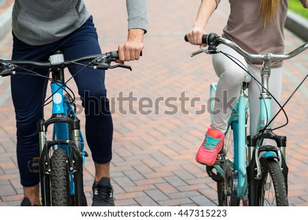 Cheerful two friends resting with bicycles