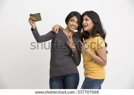 Cheerful two pretty young women taking selfie with mobile phone - stock photo