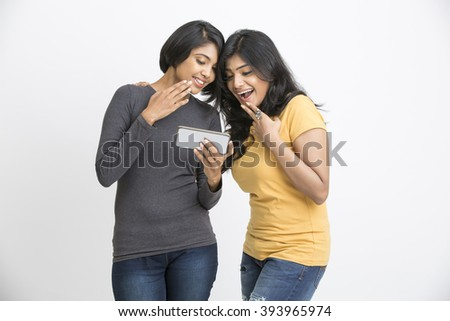 Cheerful two pretty young women watching in mobile phone