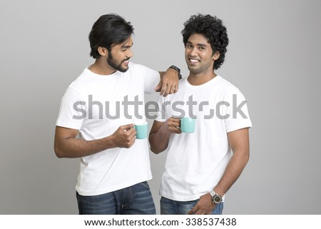 Cheerful two young men chatting with coffee cup on grey background. - stock photo