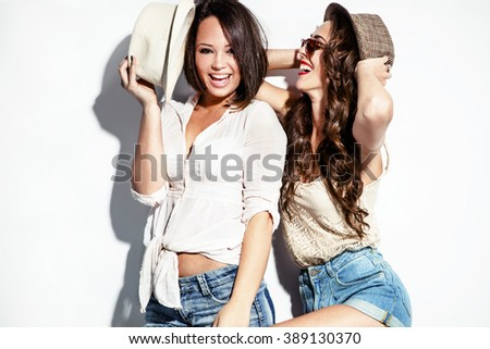 cheerful two young women in summer clothes have fun wearing jeans shorts sunglasses and hats