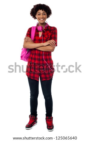 Cheerful university girl with folded arms posing with pink back pack and matching headphones.