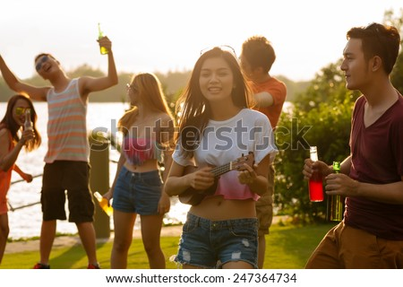 Cheerful Vietnamese friends having sunset party - stock photo