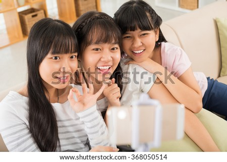 Cheerful Vietnamese girl taking selfie together