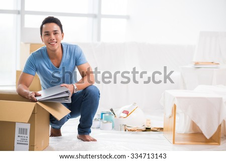 Cheerful Vietnamese man getting his belongings out of the cardboard box