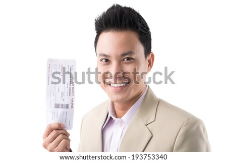 Cheerful Vietnamese man with a boarding pass - stock photo