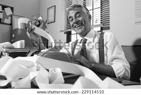 Cheerful vintage accountant smiling and working with adding machine in vintage 1950s office. - stock photo