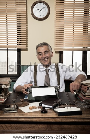 Cheerful vintage office worker sitting at desk and smiling at camera. - stock photo