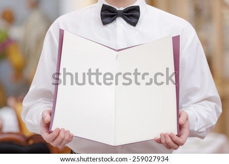 Cheerful waiter. Cropped image of handsome young waiter in shirt and bow tie holding a menu with blank pages for copy space in the luxury restaurant - stock photo
