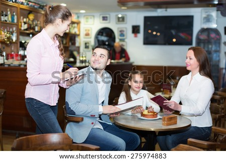 Cheerful waitress and happy family with child at cafe. Focus on weitress