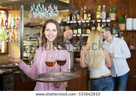 Cheerful waitress holding tray with glasses of wine in bar