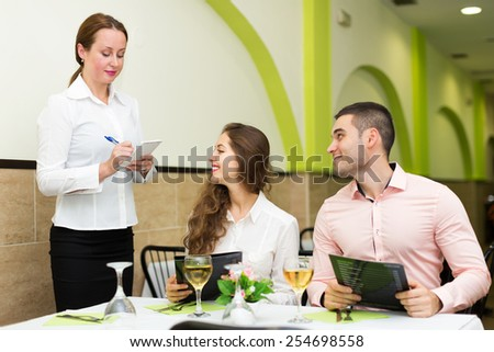 Cheerful waitress offering to young couple of the tasty dishes - stock photo