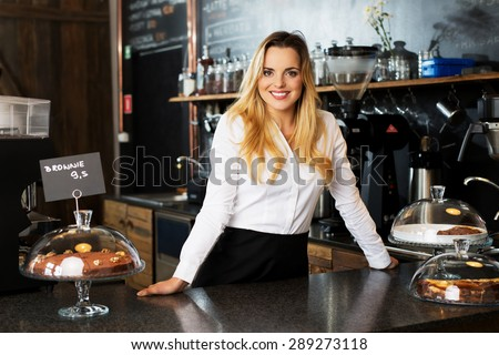 cheerful waitress standing behind the bar at cafe - stock photo