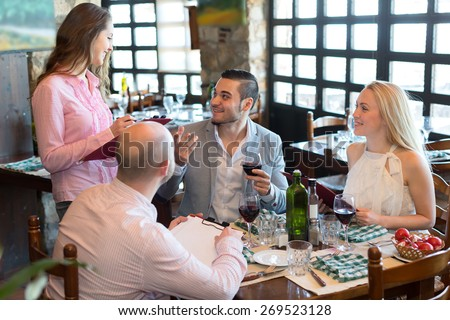 Cheerful waitress taking the order from visitors sitting at the table in a restaurant - stock photo