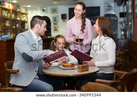 Cheerful waitress 30-35 years old taking table order and smiling at cafe - stock photo