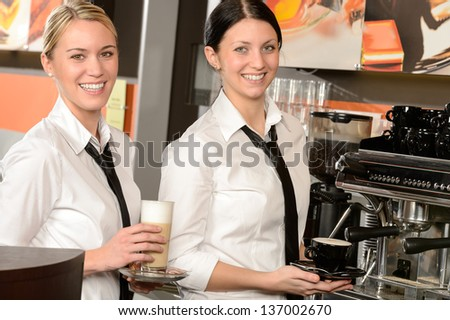 Cheerful waitresses serving hot coffee in bar in uniform