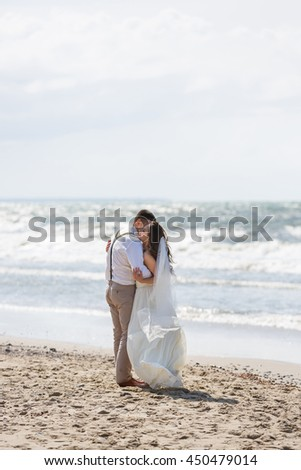 Cheerful wedding couple hugging on the beach at summer time