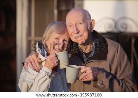 Cheerful white senior couple holding coffee mugs - stock photo