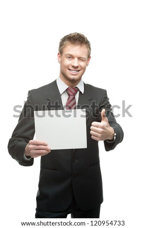 cheerful winking caucasian businessman in gray suit holding sign and showing thumb-up isolated on white background