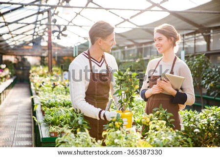 Cheerful woman and man gardeners in brown aprons taking care of plants in greenhouse and using tablet - stock photo