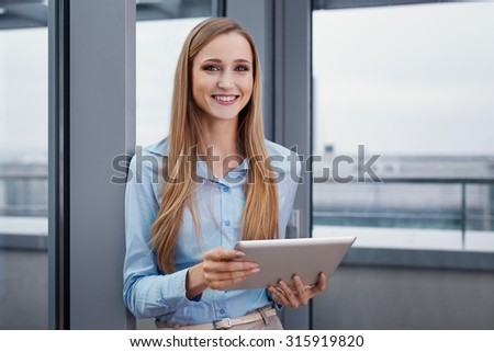 Cheerful woman at office standing with digital tablet - stock photo