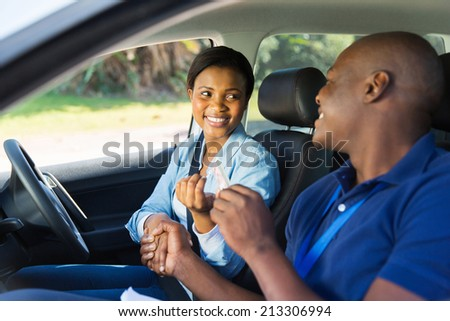 cheerful woman being handed driver�¢??s license by driving instructor in a car - stock photo