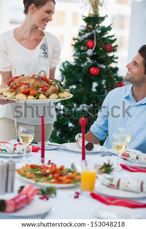 Cheerful woman bringing a roast chicken at table for christmas dinner - stock photo