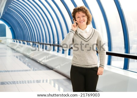 Cheerful woman calling cellular phone on the bridge - stock photo
