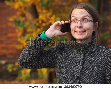 Cheerful woman calling in the autumn nature.  - stock photo