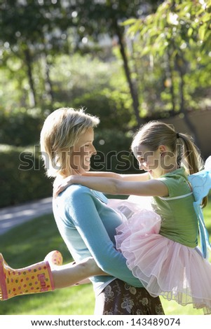 Cheerful woman carrying daughter in tutu enjoying at park - stock photo