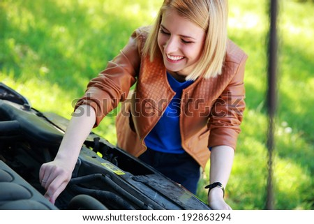 Cheerful woman checking her car engine - stock photo