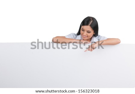 Cheerful woman. Cheerful young woman leaning at poster and pointing it while isolated on white