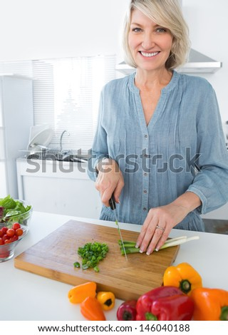Cheerful woman chopping vegetables at the kitchen counter