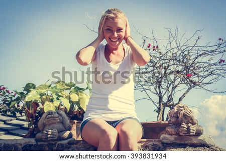 Cheerful  woman covers her ears not wishing to hear anything. She is sitting between two monkey statues. - stock photo